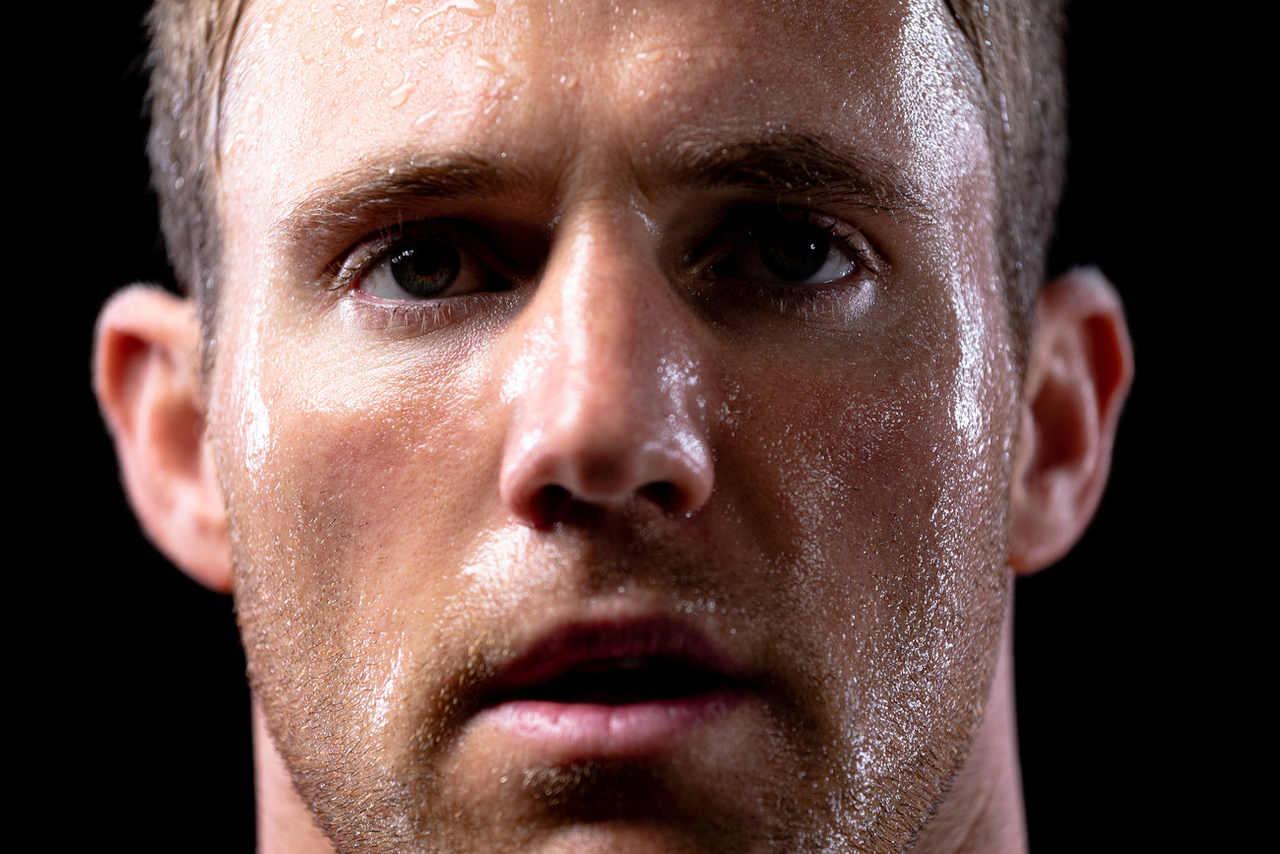 Mann mit Schweißperlen im Gesicht weiß, dass Schwitzen nach der Haartransplantation schädlich sein kann