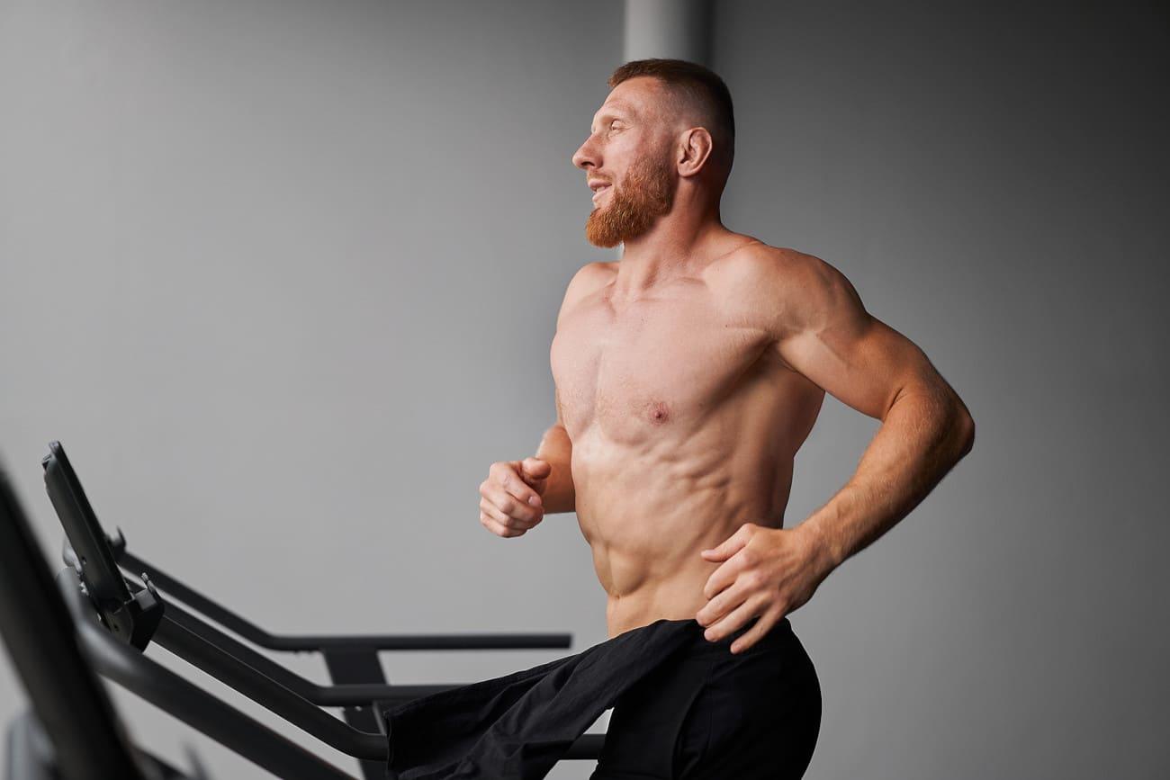 Mann läuft oberkörperfrei auf einem Laufband.