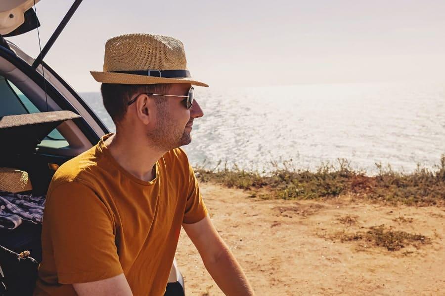Mann sitzt im Schatten mit Sonnenhut und weiß, was vor der Haartransplantation zu beachten ist