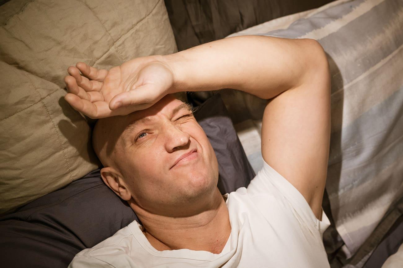 Ein Mann liegt in seinem Bett und guckt in die Sonne.