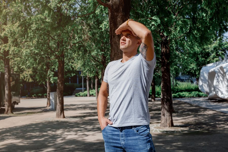 Mann steht im Schatten und schützt sich vor der Sonne als Pflege nach der Haartransplantation