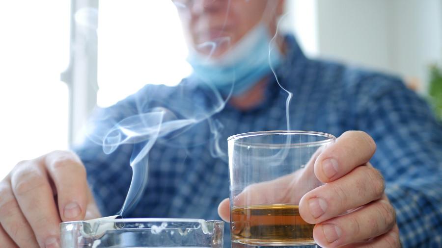 Nach Haartransplantation die ersten Tage ein Mann raucht und trinkt.
