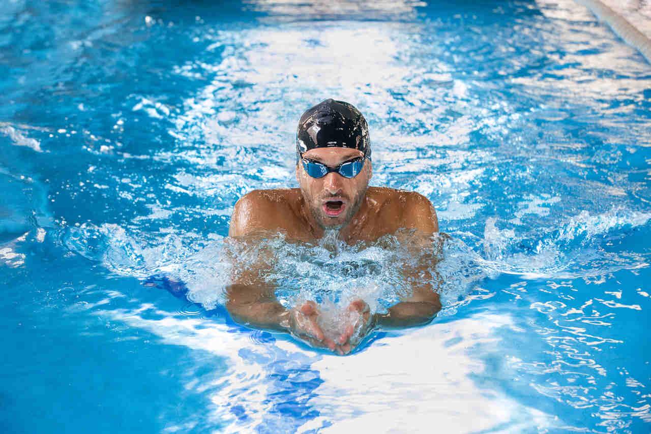Mann mit Badekappe schwimmt im Pool.