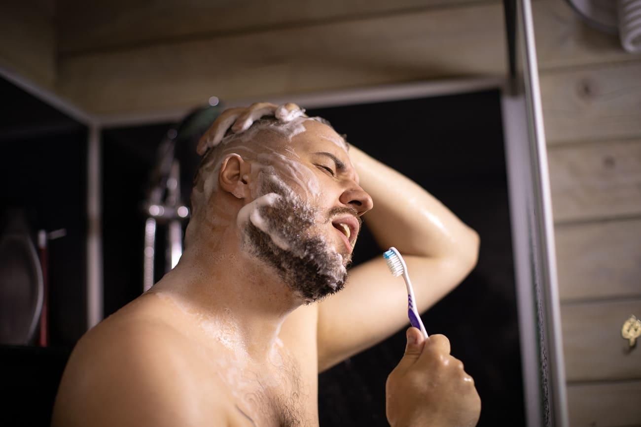 Mann putzt sich die Zähne unter der Dusche.