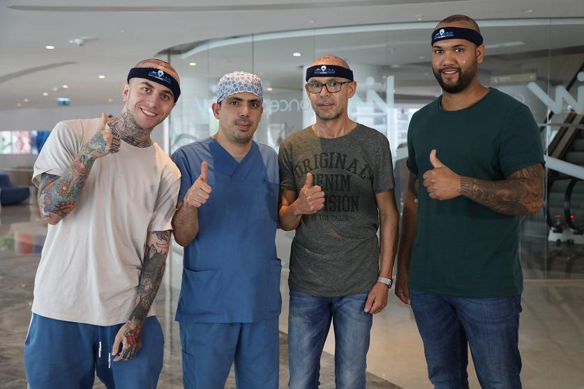 Dr. Ibrahim und drei seiner Patienten stehen mit Daumen hoch in der Lobby ohne Schwellung nach der Haartransplantation